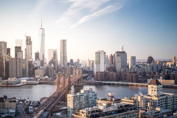 Skyline New York City Manhattan and Brooklyn Bridge At Sunset stock photo