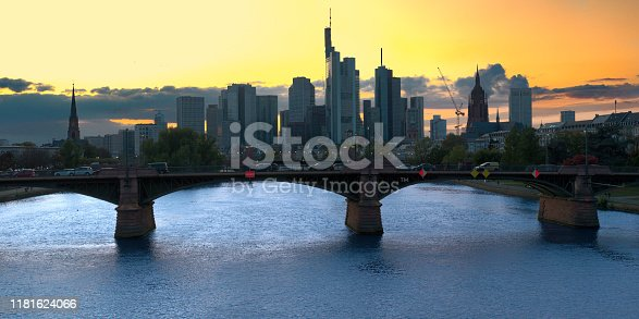 Skyline of a German city with skyscrapers shortly before the setting of the sun, with river and bridge in foreground