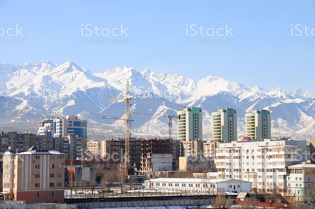 Skyline of Almaty city and snowy mountains stock photo