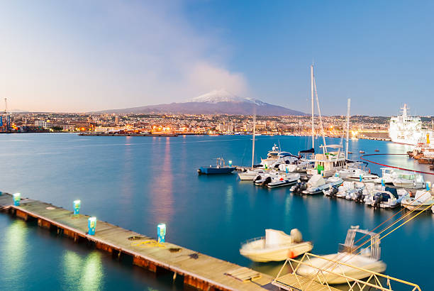 Skyline of Catania with volcano Etna after the sunset Skyline of Catania and its harbor with snowy volcano Etna in background after the sunset catania stock pictures, royalty-free photos & images