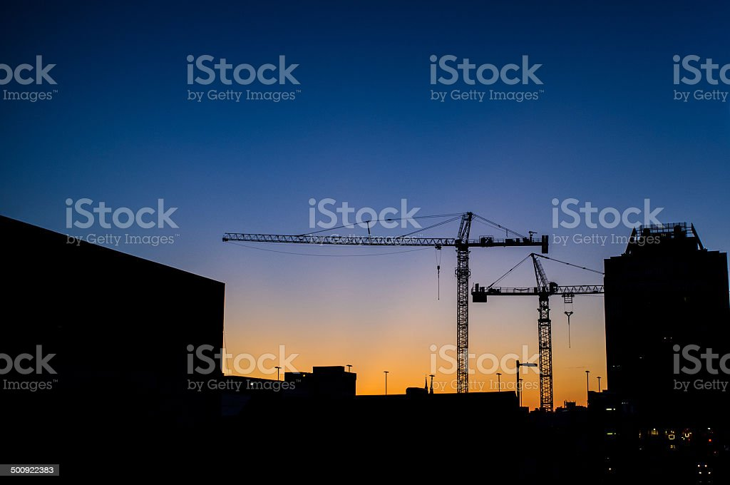 Skyline of construction cranes stock photo