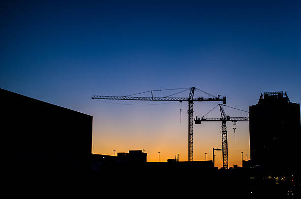 Skyline of construction cranes stock photo