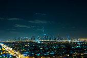 view from Jumeirah Beach Hotel on illuminated skyline of Dubai Downtown at night with Burj Khalifa