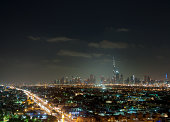 view from Jumeirah Beach Hotel on illuminated skyline of Dubai Downtown at night with Burj Khalifa