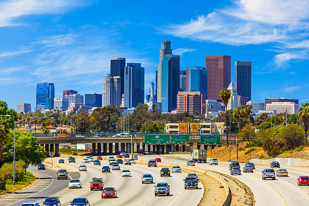 Skyline of Los Angeles with freeway traffic,CA Heavy traffic on freeway leading back to skyscrapers of Los Angele skyline. urban sprawl stock pictures, royalty-free photos & images