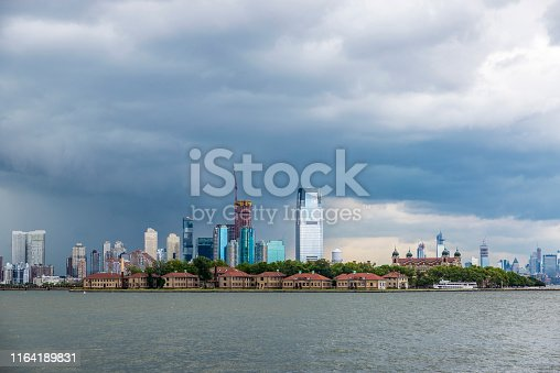 View of the skyline of modern skyscrapers of Jersey City and old buildings of Ellis Island in New York City, USA