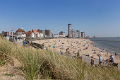Vllissingen, The Netherlands. April 22nd 2019: Boardwalk and skyline with beach of Vlissingen. Many people enjoy the unusually warm spring day in 2019.