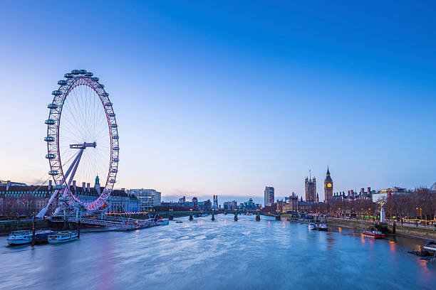 Skyline view of London before sunrise with Big Ben Skyline of London before sunrise with famous landmarks, Big Ben, Houses of Parliament, boat and clear blue sky - London, UK ferris wheel stock pictures, royalty-free photos & images