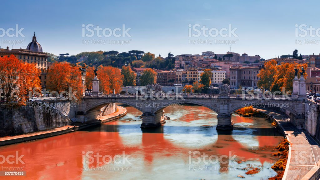 Skyline with bridge Ponte Vittorio Emanuele II and classic architecture in Rome, Vatican City scenery over Tiber river. Autumn view with red foliage. stock photo