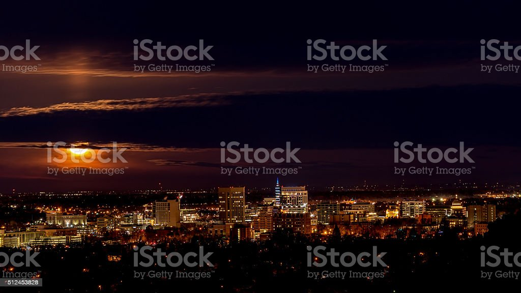 Skyling of Boise at night with full moon and clouds stock photo