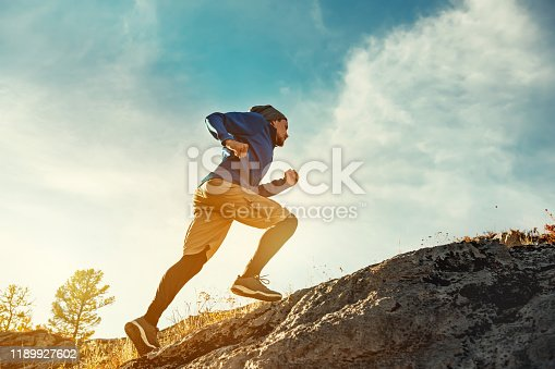 Skyrunner athlete runs uphill against sunset or sunrise sky and sun. Skyrunning concept