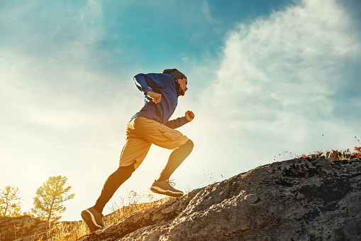 Skyrunner athlete runs uphill against sunset or sunrise sky and sun. Skyrunning concept