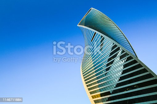 Skyscraper exterior design. Modern office building with glass facade in blue sky. Neo-futuristic architectural style. Urban view, looking up, skyline. Moscow city. Business Center.