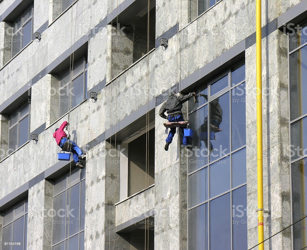 Skyscraper windows clearing, two workers royalty-free stock photo