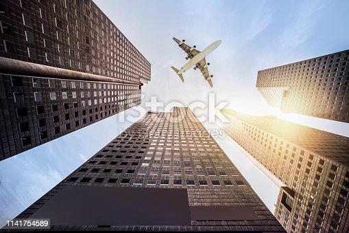 182061540 istock photo Skyscraper with a airplane silhouette 1141754589