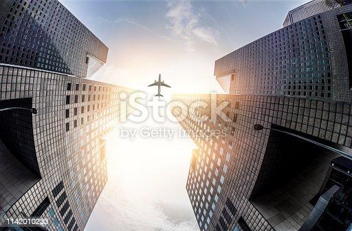 182061540 istock photo Skyscraper with a airplane silhouette 1142010233