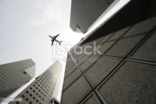 182061540 istock photo Skyscraper with a airplane silhouette 1144061134
