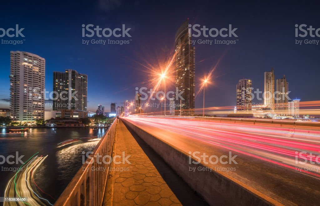 Skyscrapers and Traffic Light Trails on Taksin Bridge Crossing Chao...