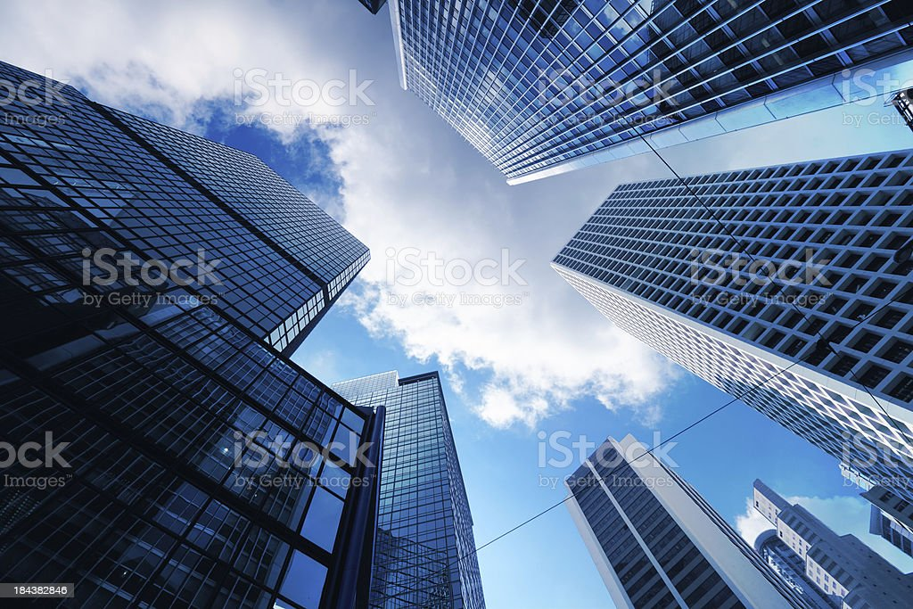 Skyscrapers from ground view with blue sky visible stock photo