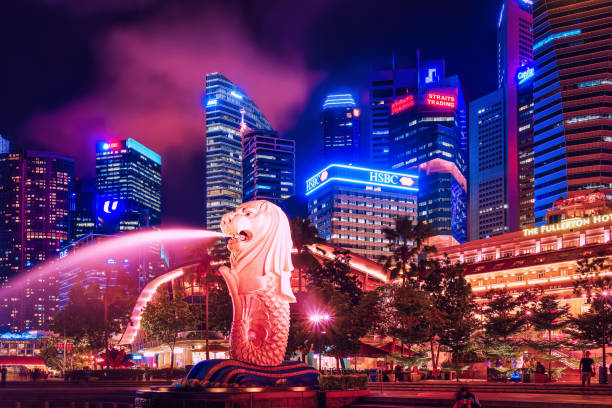 Skyscrapers Merlion statue at Merlion Park at night Singapore, Singapore - March 1, 2016: Merlion statue sprays the water from its mouth at Merlion Park in Downtown Core of Singapore at Marina Bay at night. Skyline with Skyscrapers on background merlion statue stock pictures, royalty-free photos & images