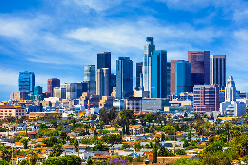 Urban sprawl fills the foreground leading back to the skyscrapers of Los Angeles skyline with cloudscape behind, California