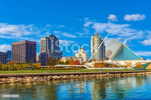 Lake Michigan with reflections fills the foreground leading back to the skycrapers of Milwaukee skyline , Wisconsin