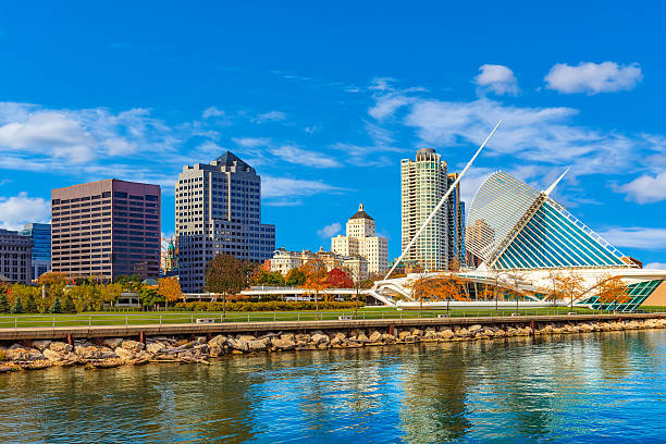 Skyscrapers of Milwaukee skyline and Lake Michigan, WI Lake Michigan with reflections fills the foreground leading back to the skycrapers of Milwaukee skyline , Wisconsin milwaukee wisconsin stock pictures, royalty-free photos & images