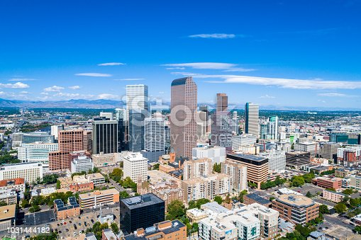 Skyline cityscape from aerial drone view looking west towards Rocky Mountain front range and downtown skyscrapers rise up in mile high city