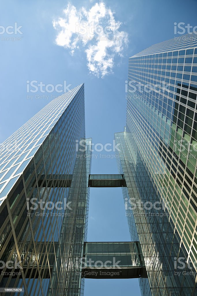 Skyscrapers with two elevated walkways against blue sky, royalty-free stock photo