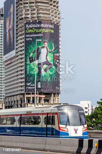 istock Skytrain passing in front of the abandoned Sathorn Unique Tower 1163184487