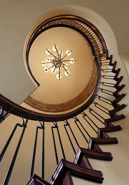 Skyward View of a Spiral Staircase and Chandelier stock photo