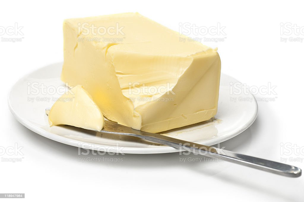 Slab of butter on white plate with knife stock photo
