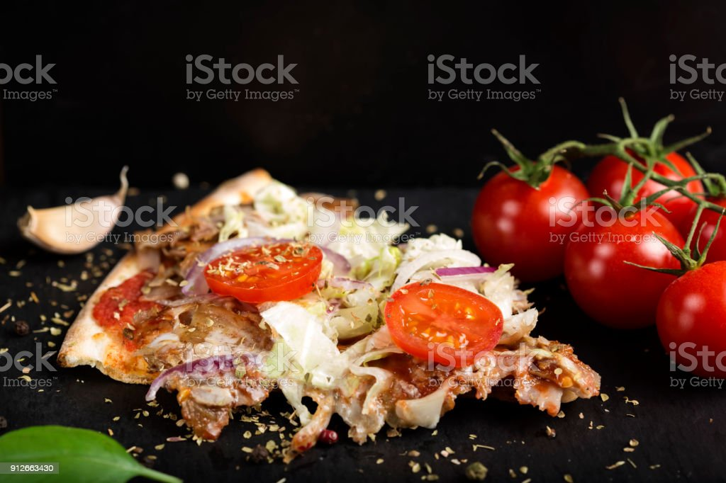 Slace of kebap pizza made with minced meat, cabbage, tomato and dried oregano stock photo