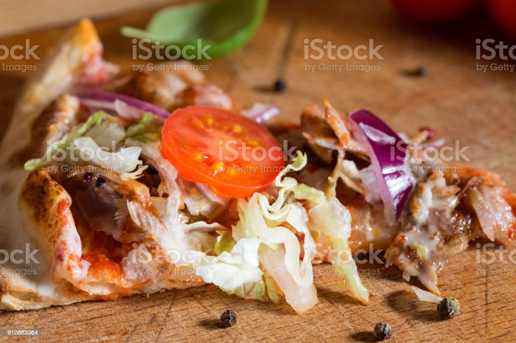 Slace of kebap pizza made with minced meat, cabbage, tomato and garlic sauce stock photo