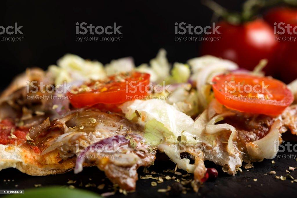 Slace of kebap pizza with dried oregano on dark slate stock photo