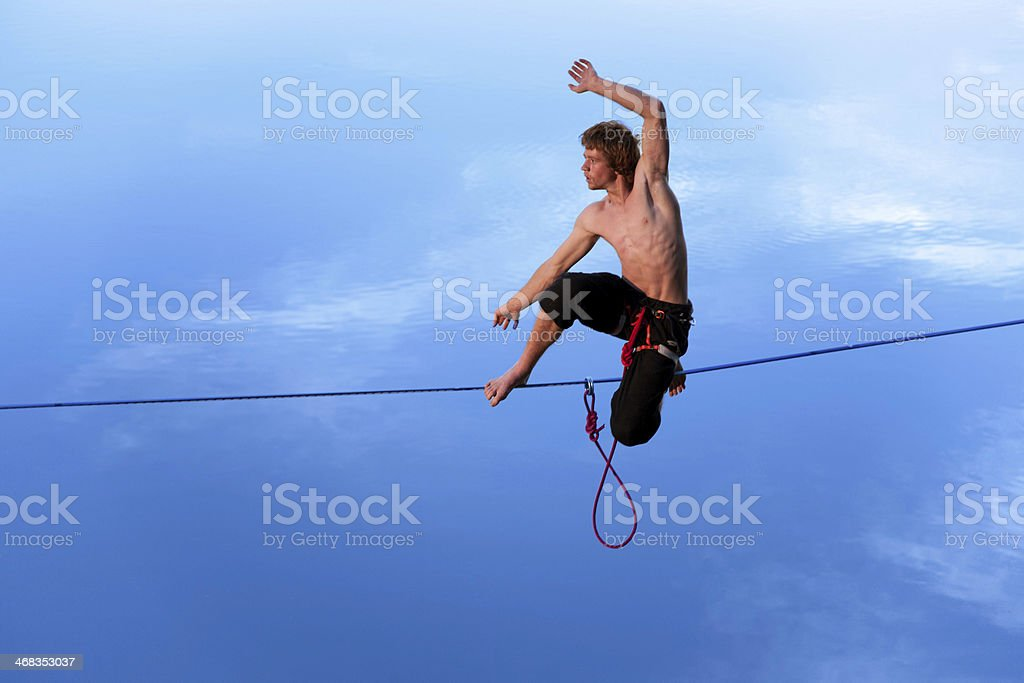 Slackling high above the water at dusk. stock photo