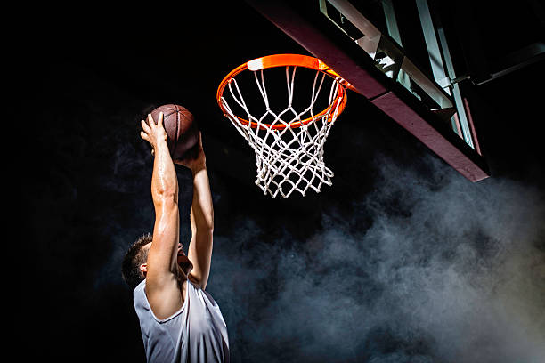 Slam Dunk Young basketball player in white jersey dunking the ball in the basket. Foggy foreground, black background. slam dunk stock pictures, royalty-free photos & images