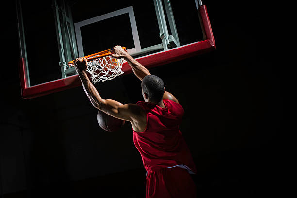 Slam Dunk Rear-view shot of a young basketball player in a red jersey in mid-air taking a dunk shot, with both hands clothing the ring. slam dunk stock pictures, royalty-free photos & images