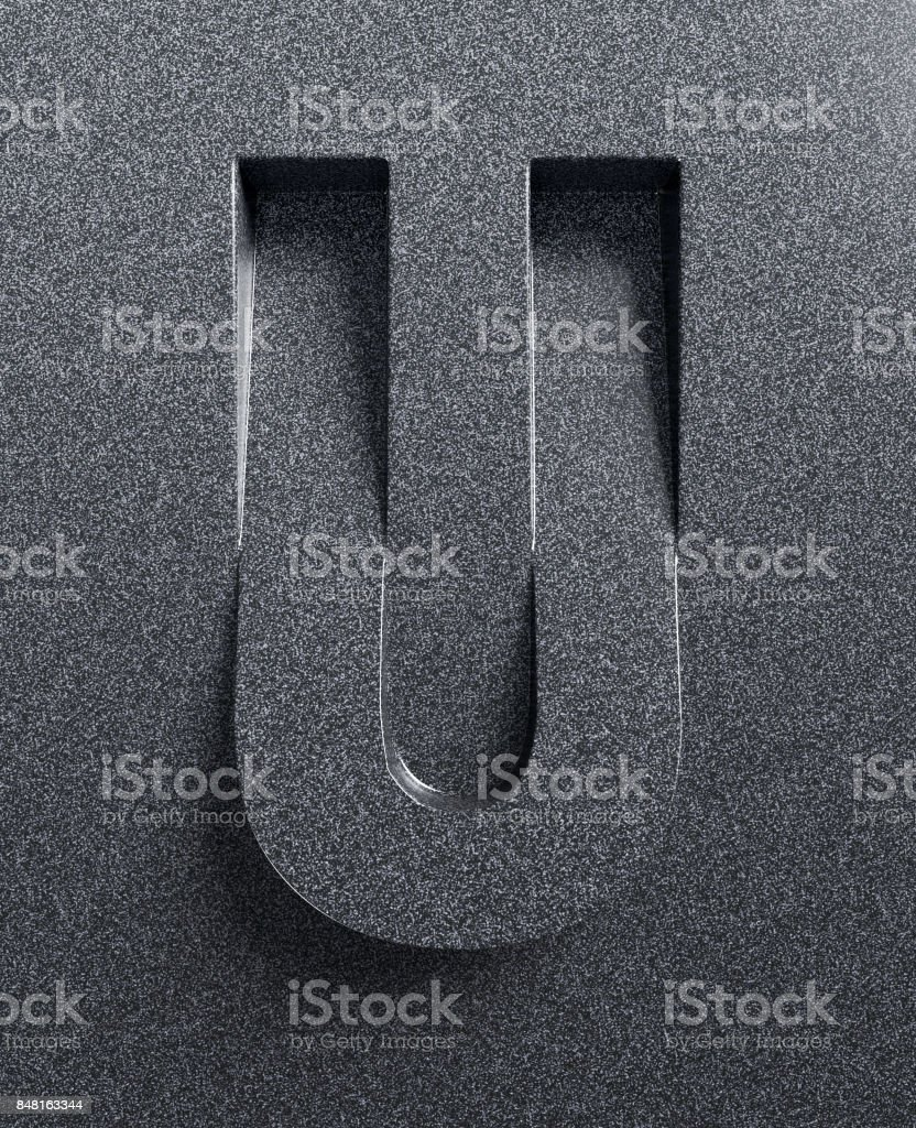 Slanted 3d font engraved and extruded from the surface letter U stock photo