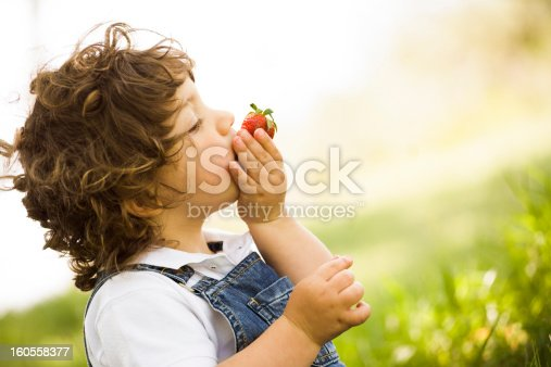 istock Slanted close-up shot of a young boy tasting a strawberry 160558377