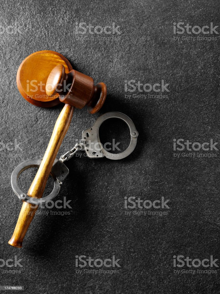 Slate Background with Handcuffs and a Gavel royalty-free stock photo