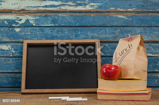 istock Slate, chalk, apple, lunch bag and books 820135540