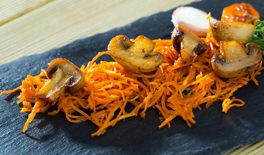 Slate of freshly fried mushrooms with carrot