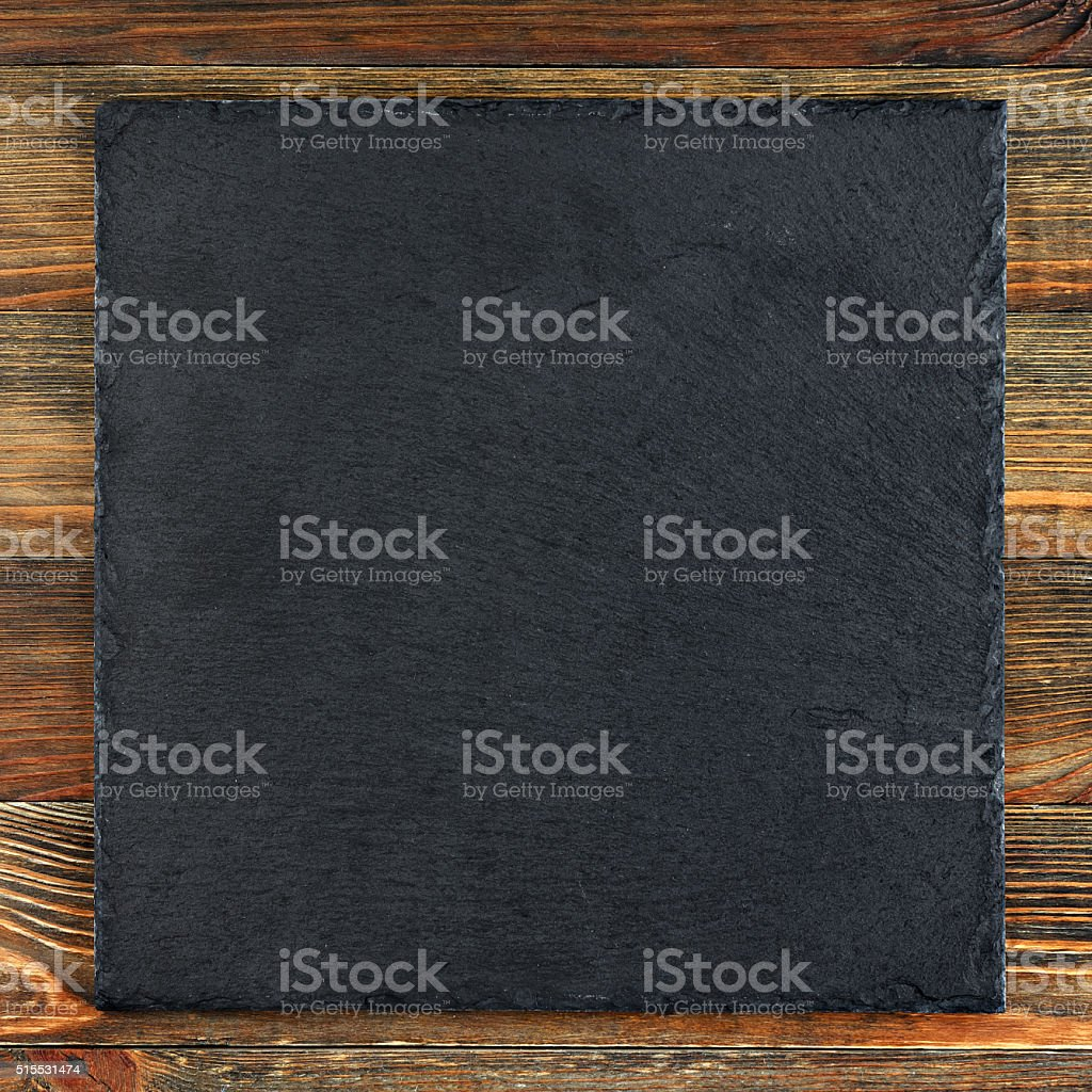 Slate plate on old wooden board stock photo
