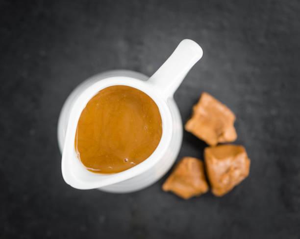 schiefer tafel mit karamell-sauce - karamellsirup stock-fotos und bilder
