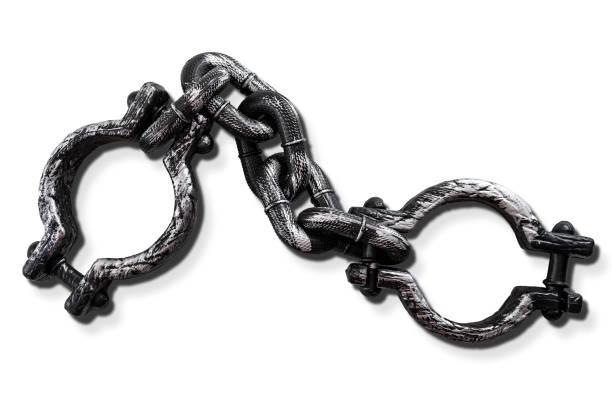 Concepto de esclavitud y servidumbre con grilletes de acero fuertes aislados sobre fondo blanco con un recorte de trayectoria de clip - foto de stock