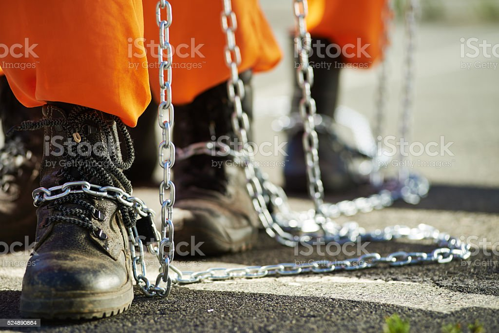 Slavery Close-up of male feet in chains Adult Stock Photo