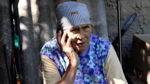 Slavic senior rural woman using phone at village stock photo