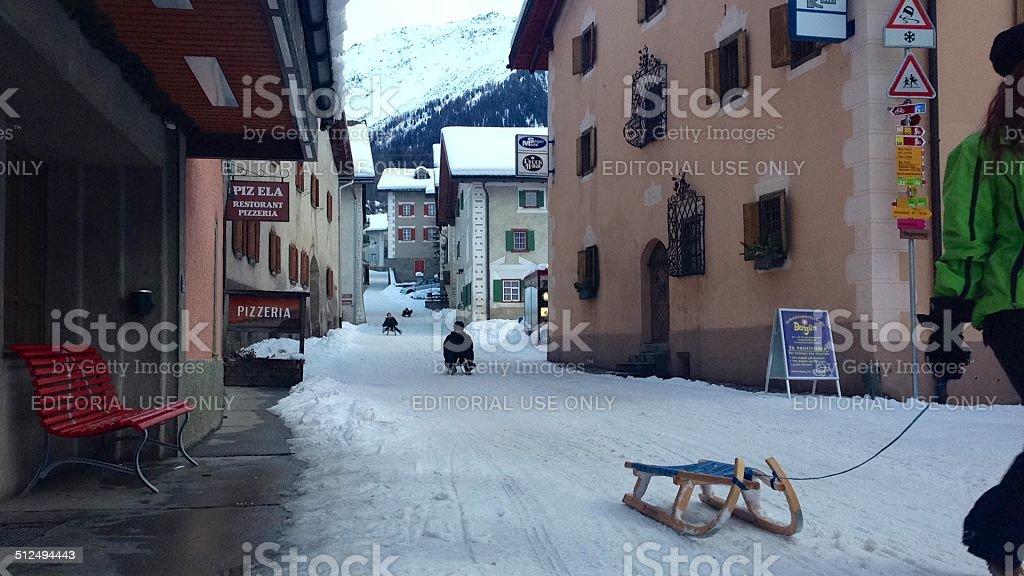 Sledders on the main street of Bergün, Switzerland stock photo