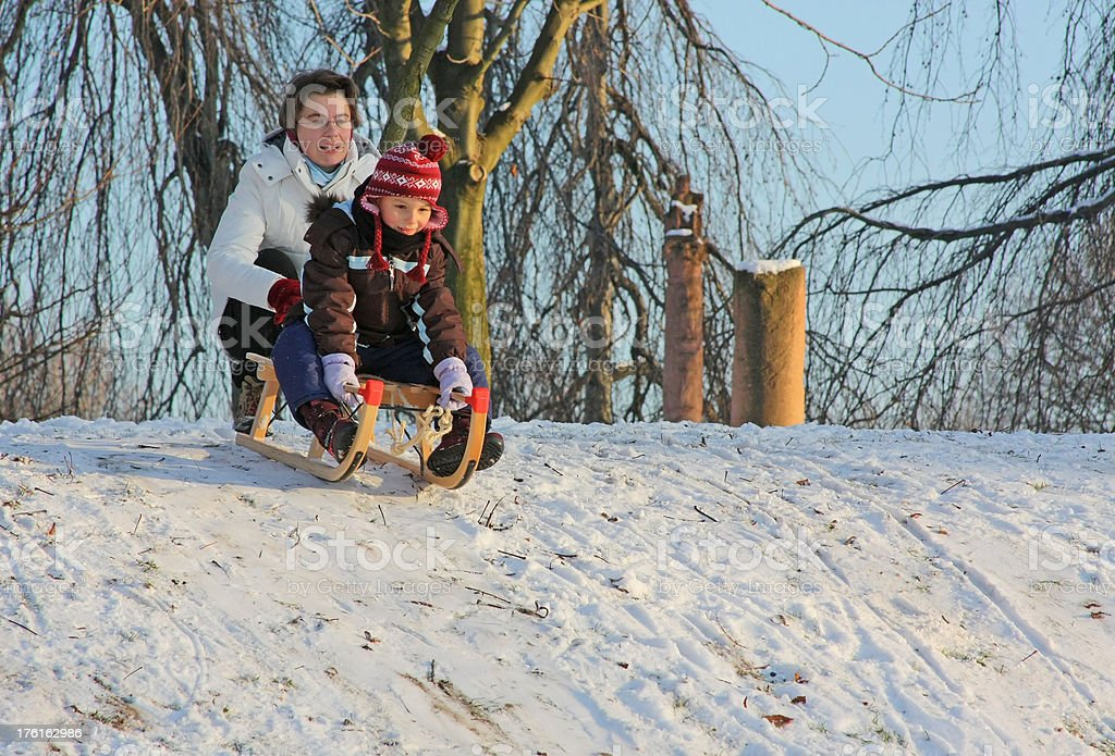 Sledding fun - mother and daughter sled downhill royalty-free stock photo
